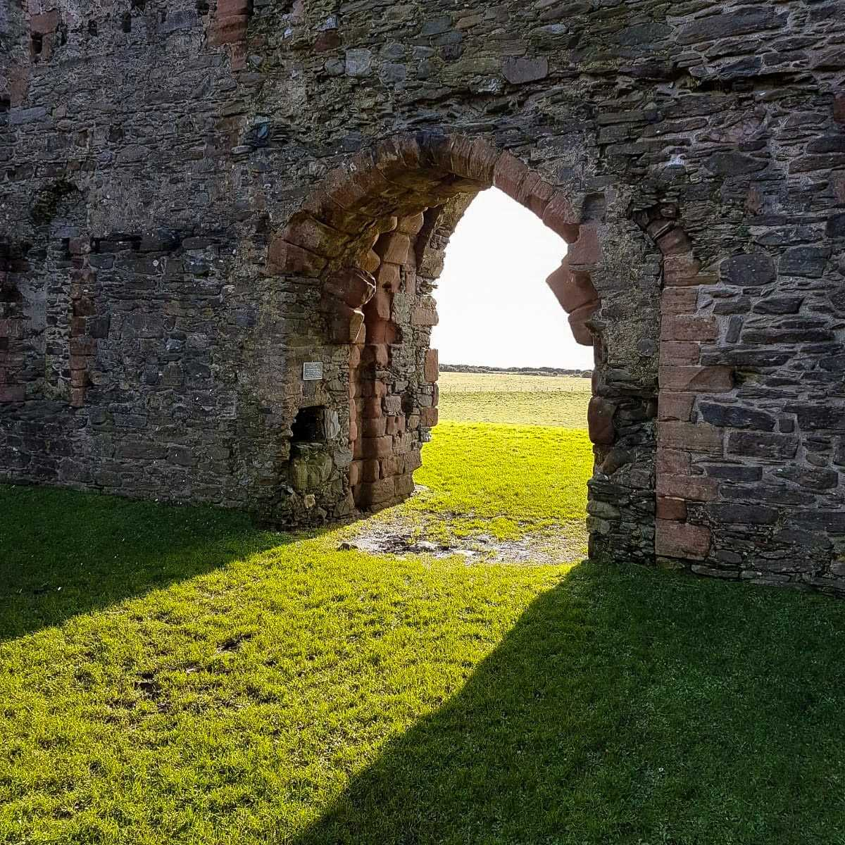 It's not a hugely interesting picture. A tall wall of stones, rising out of shot, stands on a slightly muddy grass field. In the centre of shot is an doorway opening in the wall, sunshine coming through, looking out onto a farmer's field.