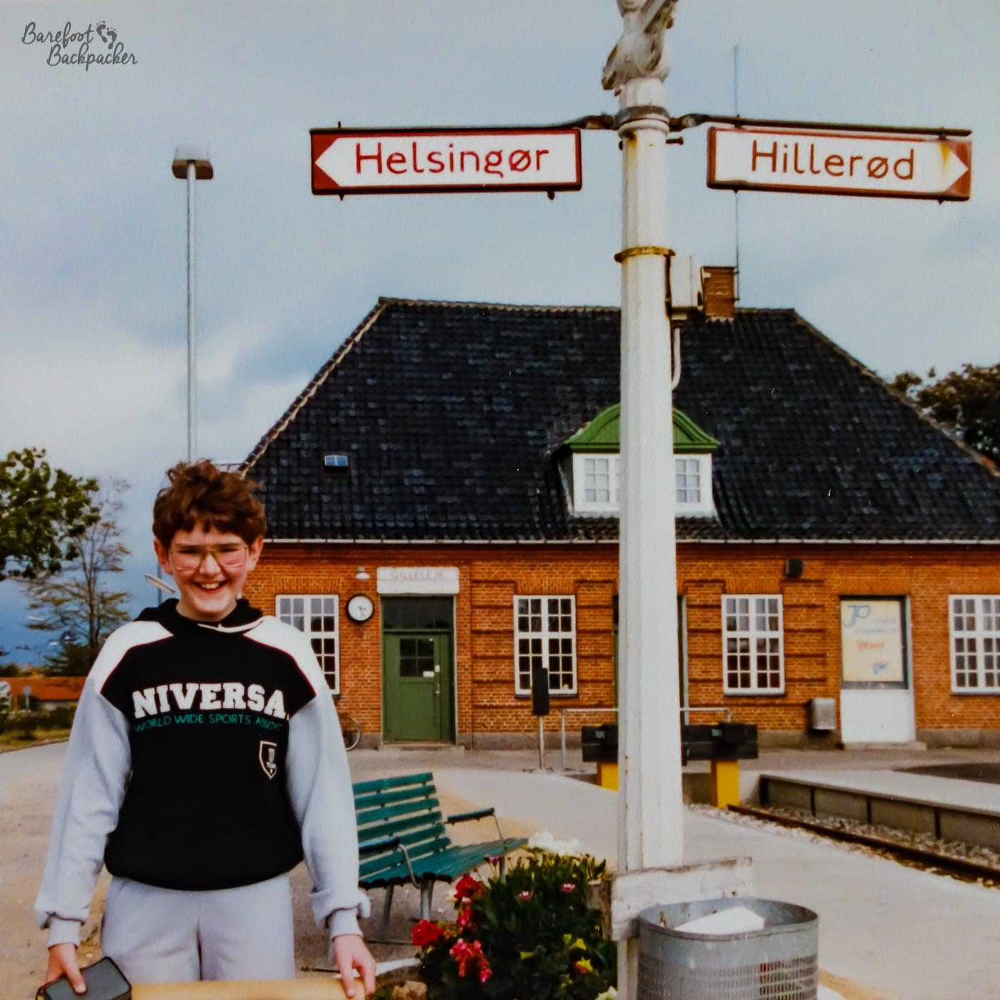 A young boy (11 years old) stands on a railway station platform. He seems happy. Geeky glasses, btw. Huge signpost behind indicates one platform is to Helsingor, the other is to Hillerod. A large station building stands in the far background. It's overcast.