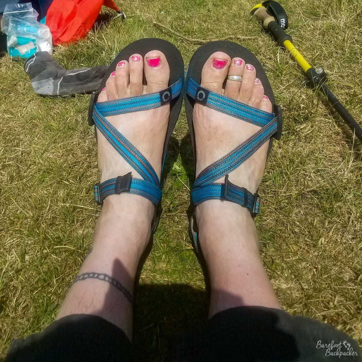 My feet in a pair of Xero sandals, taken somewhere on the Norfolk Coast Path, in England. The rubber upper sole of the sandal is smooth and black rubber, and the straps holding my feet in place are a mottled blue.
