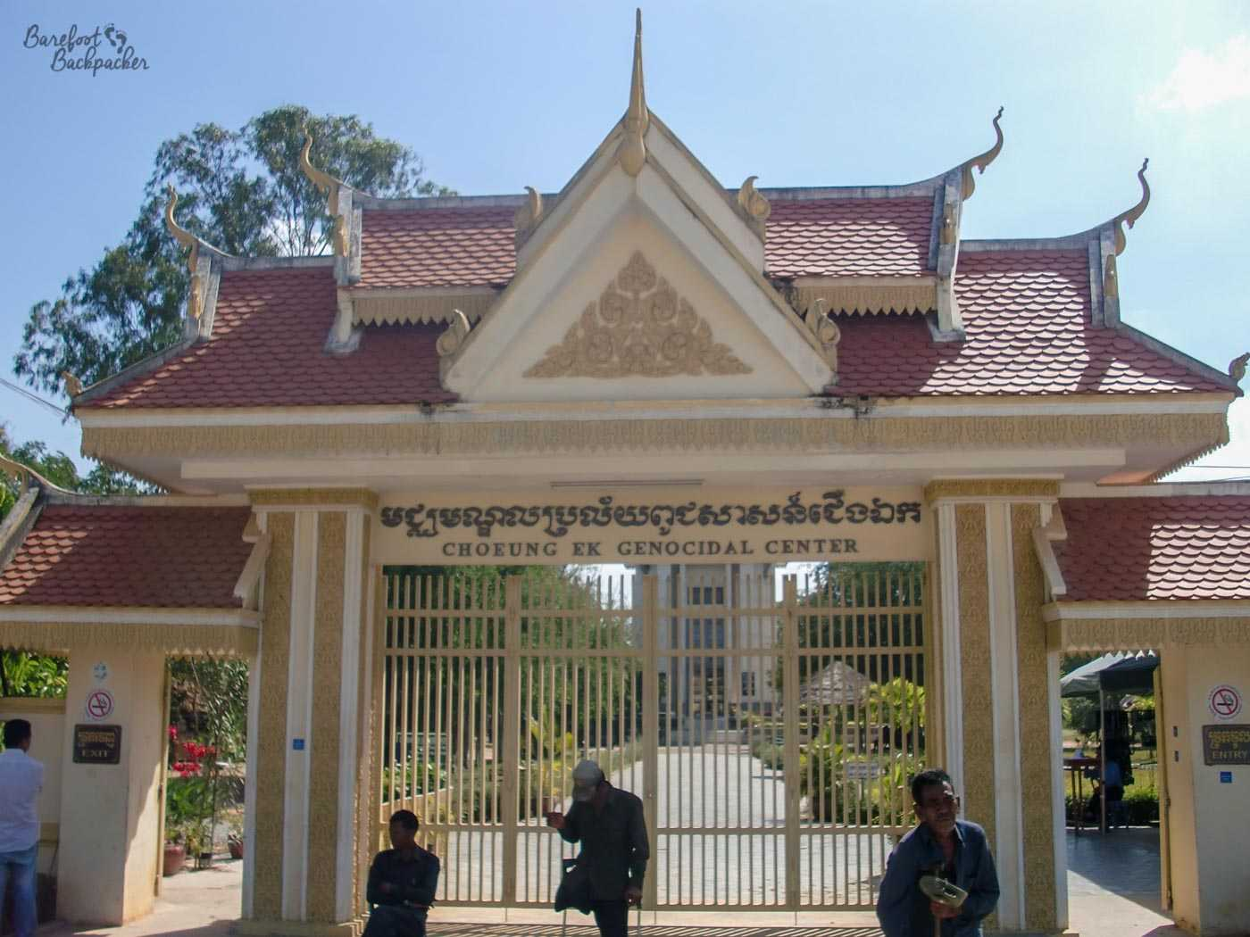 The entrance to Choeung Ek – The Killing Fields. It has the feel of a Buddhist temple in design, with multiple sloping roofs and triangles. Behind the gate is a straight road leading to a 'stupa'.