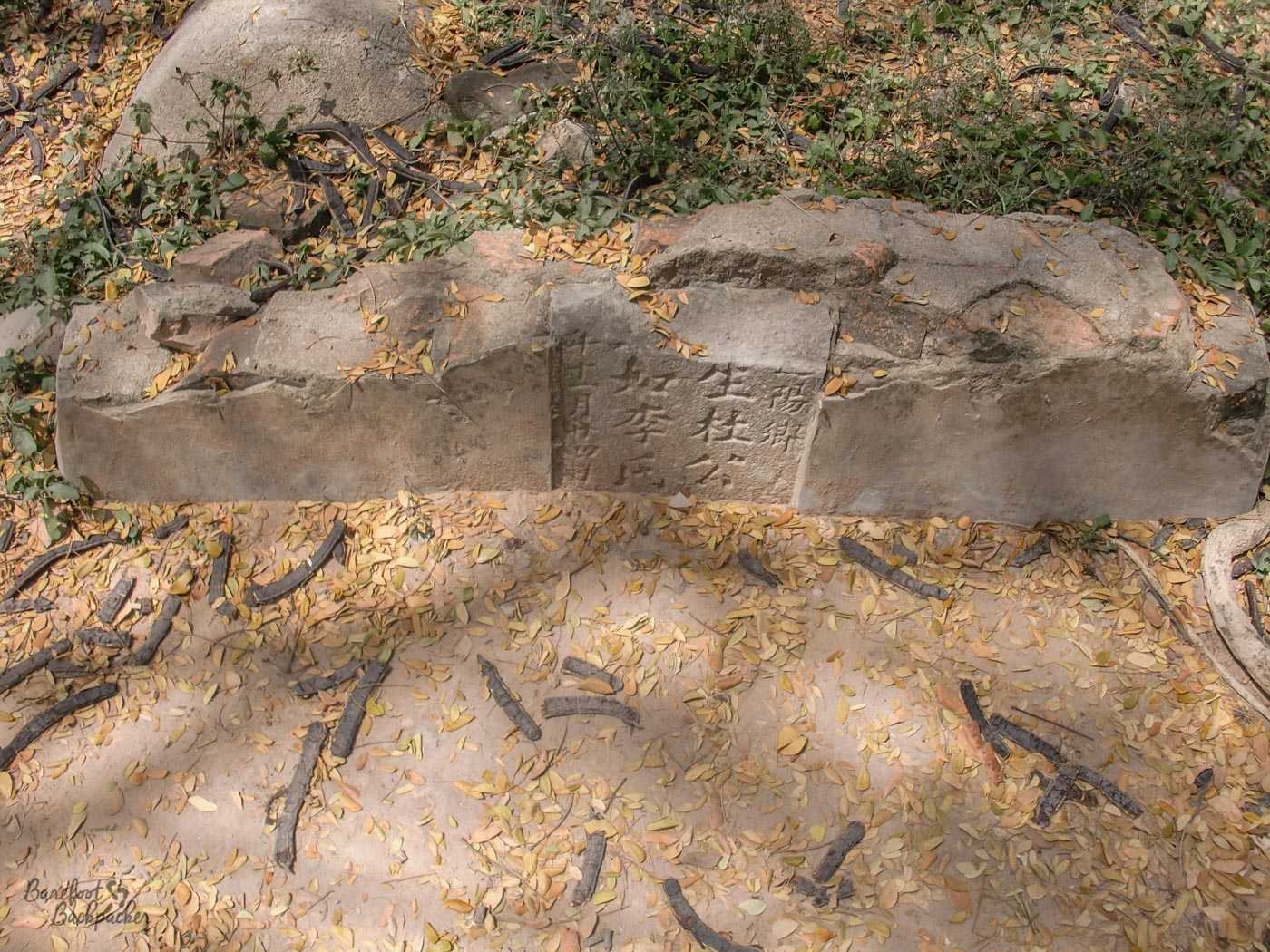 The remains of a Chinese grave. It's been broken off not far from the ground, so only a small selection of Chinese characters remain visible.