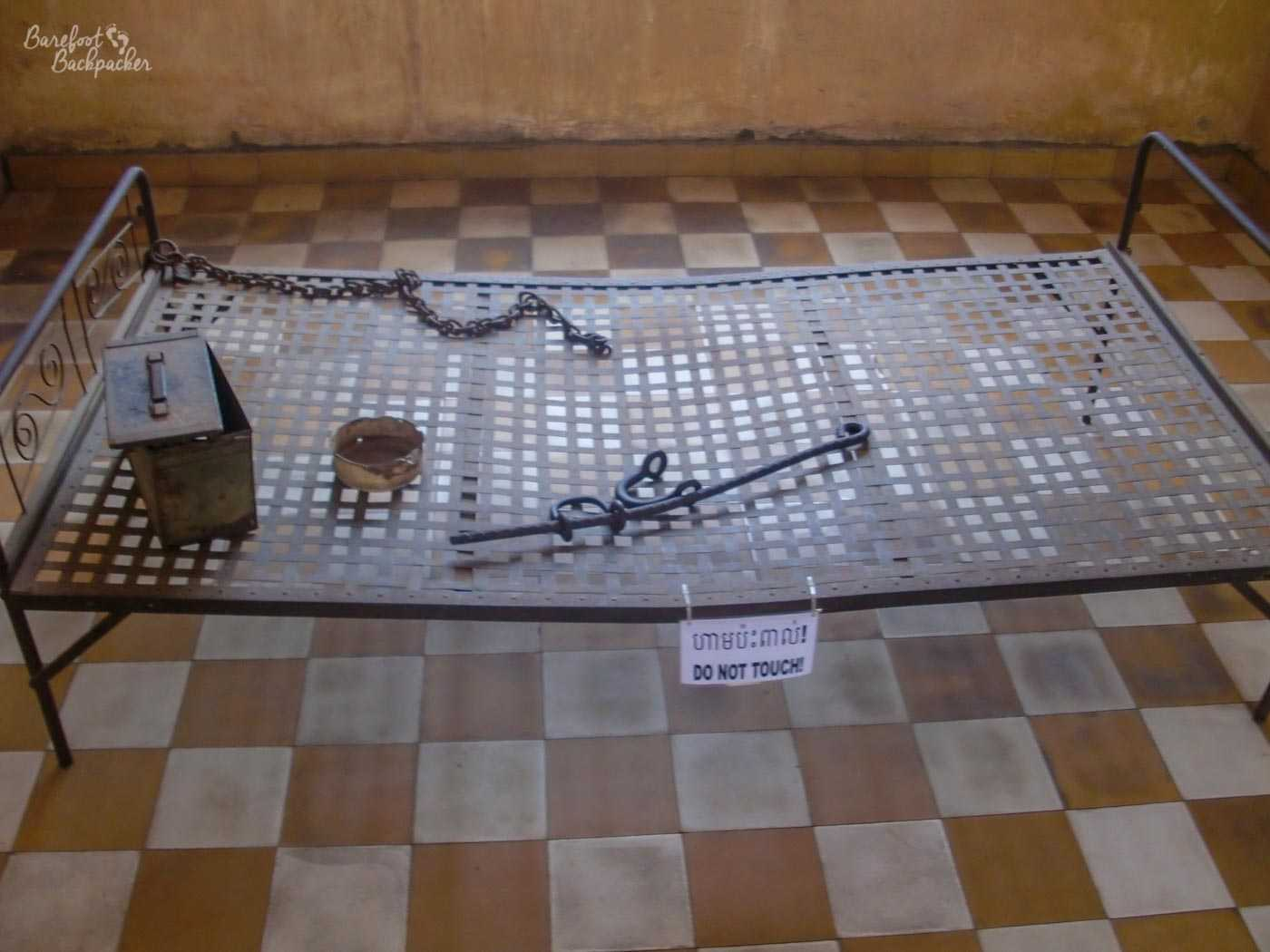 The bare frame of a metal bed in one of the larger rooms of Tuol Sleng (an old classroom, presumably), on a chequered tile floor.  A chain is attached to one of the corners of the frame. On the bed are three other objects – a metal box, a circular rusted ashtray, and a long metal object with a hook at one end and what looks like a clamp at the other.