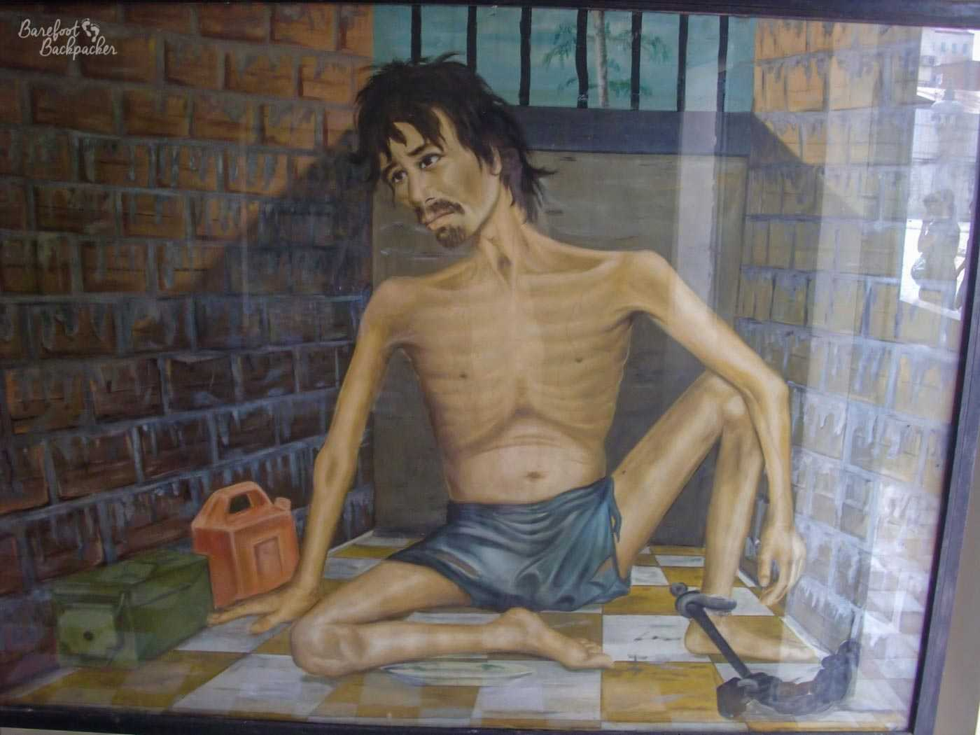 Painting by one of the few survivors of Tuol Sleng. It's one of the milder ones, showing an emaciated man in a cramped cell, bars behind him. His left ankle is shackled to a chain, and he is only wearing a loincloth. The only other things in the cell are a box and a jerry can.