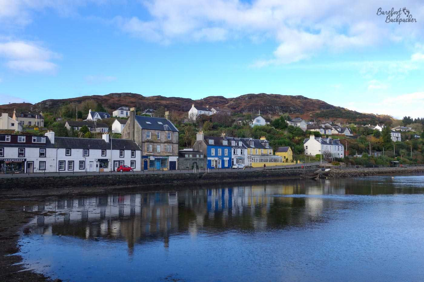 The village of Tarbert, on the shores of Loch Fyne. A series of multi-coloured low-rise buildings stand on the quayside. They are reflected in the still waters of the loch. Behind the cottages are some dark green, lush hills, and behind that, at the top of the picture, the sky is blue.