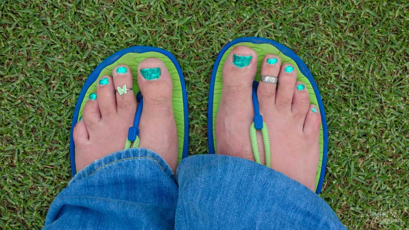 My feet in minimalist sandals, taken in Australia. The rubber upper sole of the sandal is lime green, on a blue under-base. These sandals have a blue piece of plastic between the toes, and a green cord is attached to them which fixes onto the back of the sandal, which you can't see because my jeans are in the way.