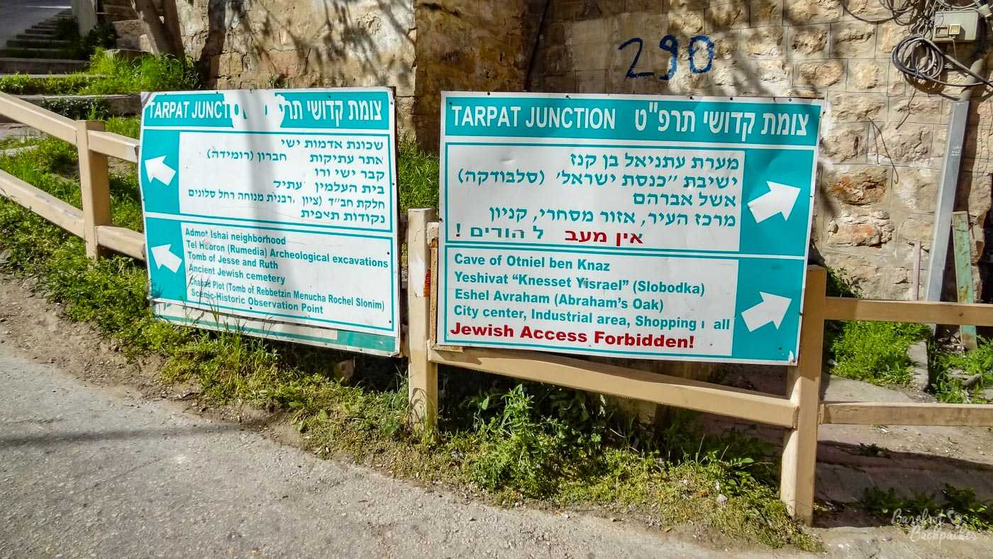 A signpost in English and Hebrew (it's in Hebron, in the Holy Land), directing people towards various local sites, including, to the left, the Ancient Jewish Cemetery, the Tomb of Jesse and Ruth, and a couple of archaeological excavations and lookout points, while to the right is the Cave of Otniel ben Knaz, Abraham's Oak, and, with big red letters saying 'Jewish Access Forbidden!', the city centre, industrial area, and shopping mall.