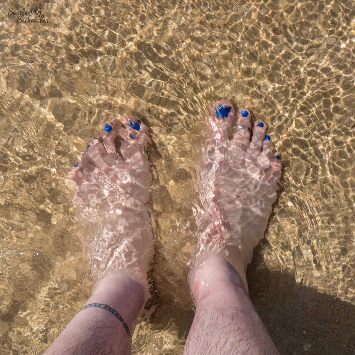 My bare feet in some shallow water at Napcan beach, on the Philippine island of Palawan. The water is very clear; the only disturbance being slight movement of the sand underfoot. My toenails are a sharp blue, still clearly visible under the water.