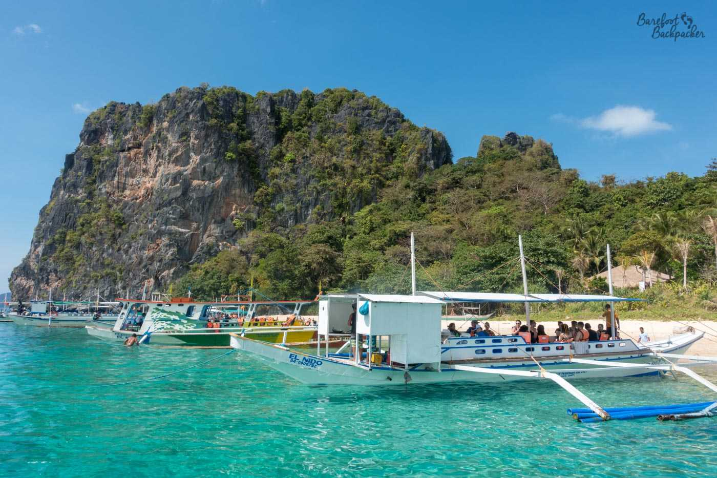 A series of boats full of tourists are lined up in the sea just off the beach of an island in Philippines. The sea is transparent and more green than blue. Behind the boats is a small but towering bush-covered cliff. The sky is very, very blue.