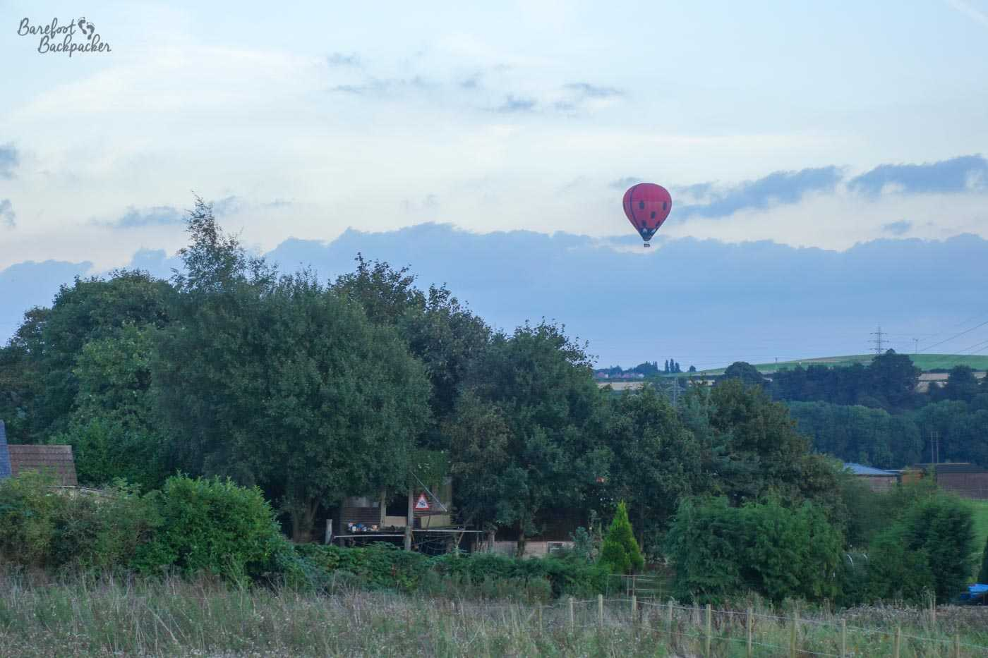 A hot air balloon, red with five black spots, floats in the early dusky skies over Kirkby-in-Ashfield, Nottinghamshire, England. The sky is largely clear with just a layer of faint white cloud. The balloon is floating over a landscape of trees, fields, low hills, and electricity pylons. Parts of a house are visible on the left.