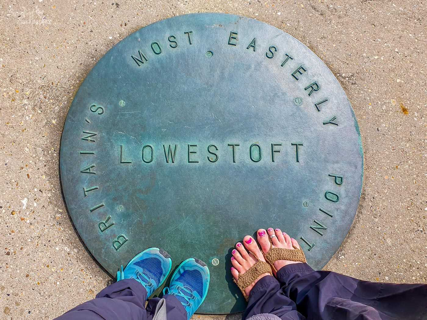 On the cement ground is a blue-grey metallic plaque that says 'Lowestoft. Britain's most easterly point'. Resting on the plaque are two pairs of feet - one in blue trainers, the other bare with brown crochet coverings and red toenails.