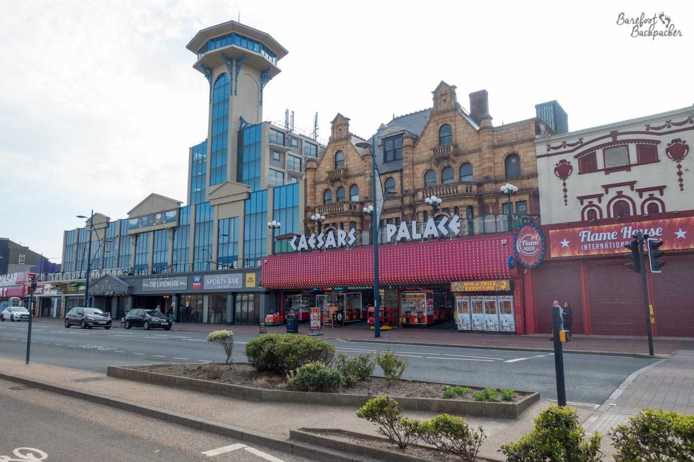 Great Yarmouth Promenade. A pub with a modern look stands next to a Victorian brick building called 'Caesar's Palace', serving as a garish amusement arcade, with a closed restaurant called 'Flame House' next to that.