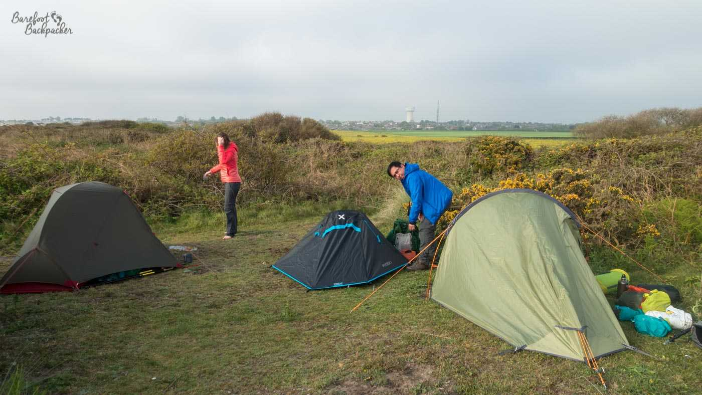 Three tents have been put up in a piece of flat grassland just off the Norfolk Coast Path. The area is surrounded by bushes. In the distance are green fields and, on the horizon, buildings and a possible water tower that indicate the town of Caister. By the tents are scattered bags; a man is bent down examining something and a woman is standing on the left, shading her eyes from the sun.