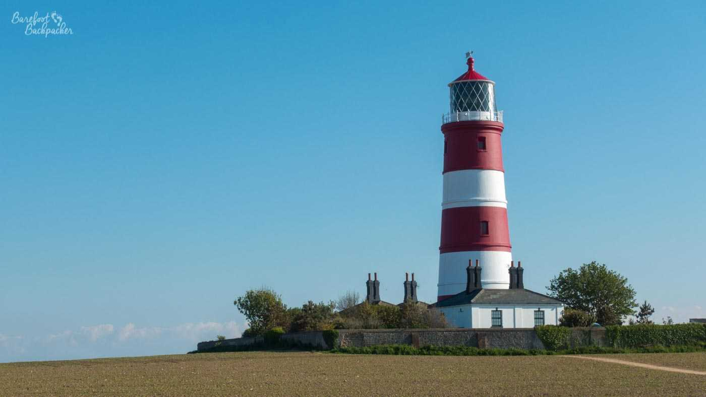 Against a clear blue sky, and standing on a flat light brown landscape, is a lighthouse. It is striped red and white, is topped with a cylindrical frosted glass window, and has a small cottage at the bottom.