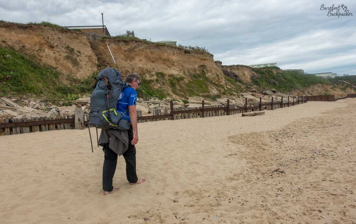 The Barefoot Backpacker hikes along the sand of Bacton beach. Behind him, huge cliffs loom. Odd as it sounds, this is exactly where the Norfolk Coast Path runs.