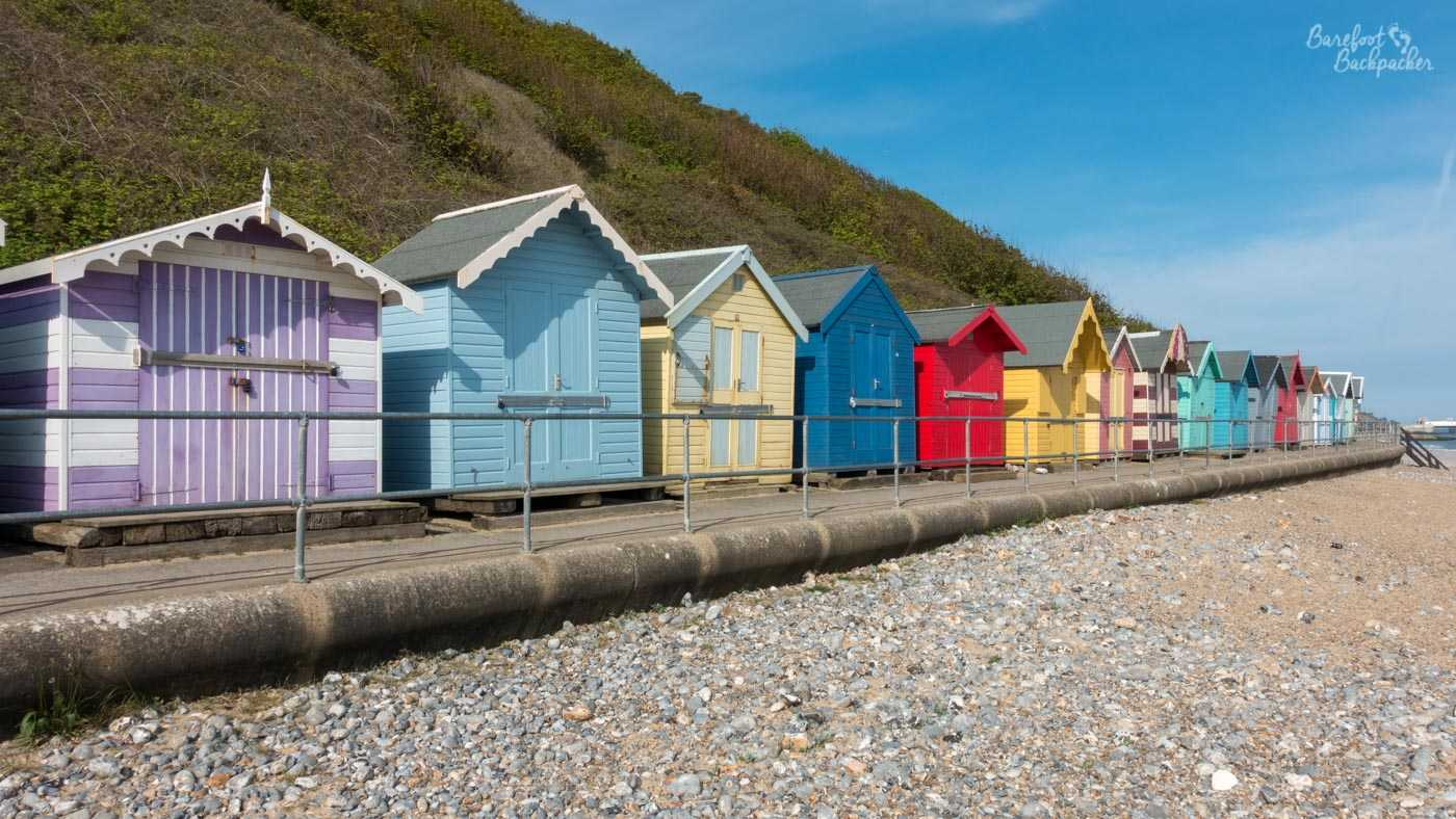 A line of brightly-coloured huts in pastel shades stand on the beachfront, in front of a cliff and a clear sky. The beach itself is more shingle than sand.