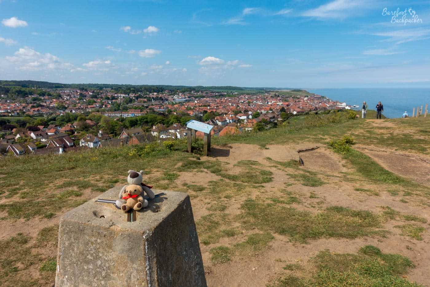 Two small soft toys sit on top of a trig point. Behind them, a hilltop drops away to reveal the vista of a town, mainly housing. To the right, the sea is visible as it merges with the sky.