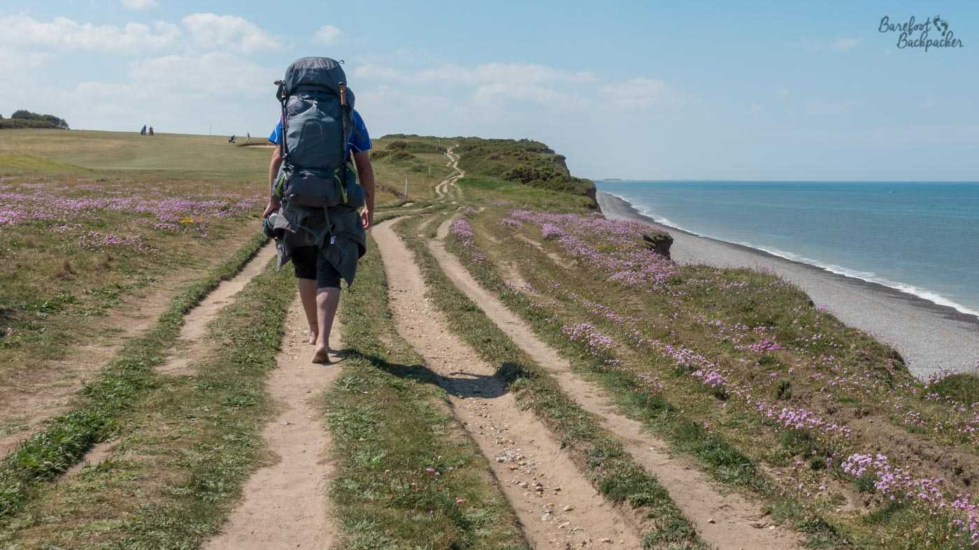 A man carrying a large blue/grey backpack, wearing black trousers that come to just below the crack of the knee, is hiking barefoot along the Norfolk Coast Path, here being a smooth trail along an otherwise grassy and flower-covered cliff edge. The trail can be seen to disappear into the distance. To the left is a golf course, to the right the cliff cuts sharply to a stony beach and the sea.