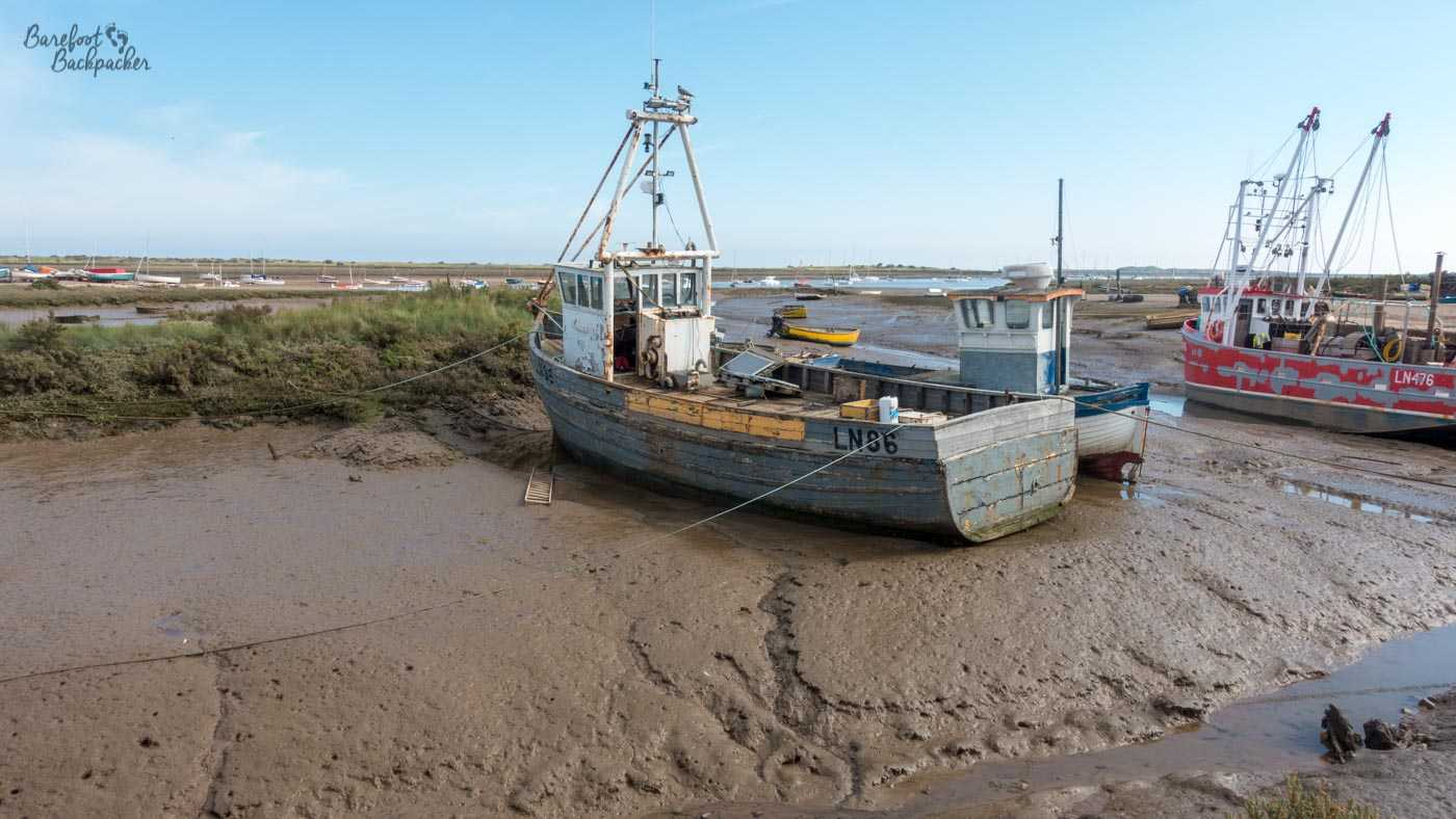 A wooden ship, old and very much the worse for wear, stands stuck in a mud flat in what used to be a harbour. A grassy bank lies behind, and then in the distant background, a whole series of small boats. To the right, another wooden ship, with rusted paint jobs, stands equally forlorn