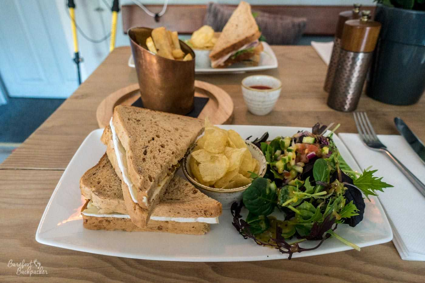 Cheese sandwiches, a bowl of crisps, and some leafy salad are on a white rectangular plate with curved edges, on a wooden table. Behind is a metal cylinder of chips, a small ceramic pot of sauce, and some large salt and pepper shakers. A similar plate with sandwiches and crisps is blurry in the background.