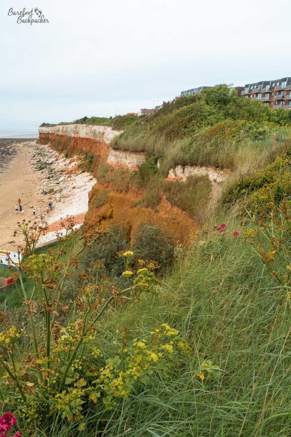 A cliff with rock in several colours disappears into the distance. The rock is sort of red/green at the bottom, orange in the middle, and white at the top. This contrasts well with the yellow sand to the left and the green grass on the cliff edge on the right.