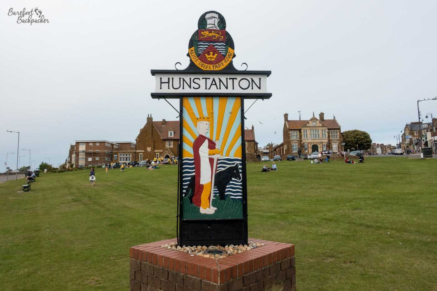 Hunstanton's main 'village green'. The village sign takes centre stage - a regal figure standing with a long sword in the ground, in front of what looks like a horse, with a representation of the sea in the background. As for the green itself, it's on a slope. There are some old buildings in the background, possibly a pub, and many indistinct people sitting, standing, playing sports on the grass.