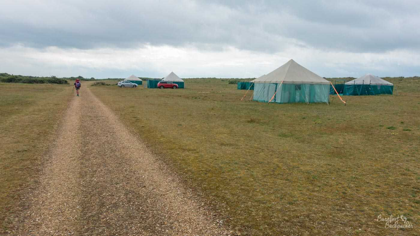 Wide open space; flat grassland, a slightly gravel track makes its way through. Becky is hiking away in the distance. There are some yurt-like structures on the right - generally rectangular and made of tent fabric. A couple have cars in front of them.