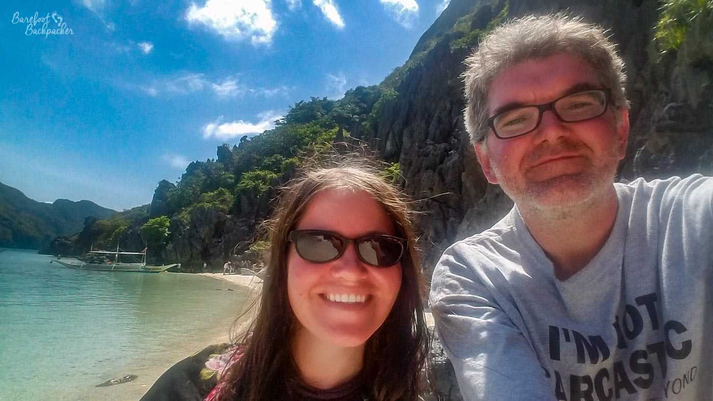 Me and Laura standing on the beach at Helicopter Island, in Philippines. The sun is shining, the water behind us is clear and there is an open-sided boat on it, and there is a relatively small cliff edge behind us to the right.