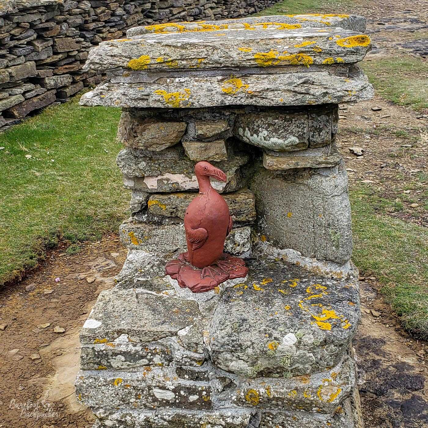 On a stone plinth on a cliff edge is a small red statue of a bird. It looks a bit like a penguin?