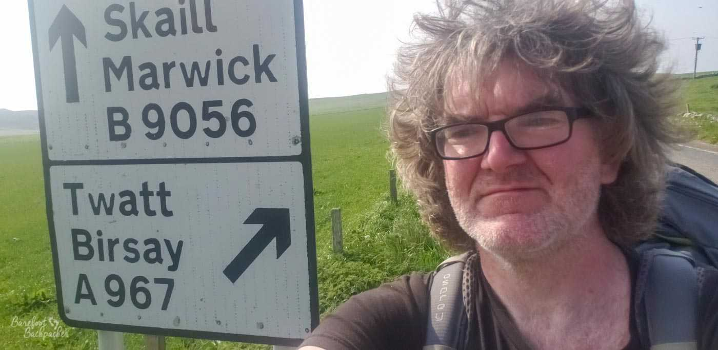 Person with messy hair and a backpack stands to the side of a road signpost. The directions on the signpost are Skaill and Marwick on the B9056, with an arrow pointing straight up, and Twatt and Birsay on the A967 with an arrow pointing at the person.