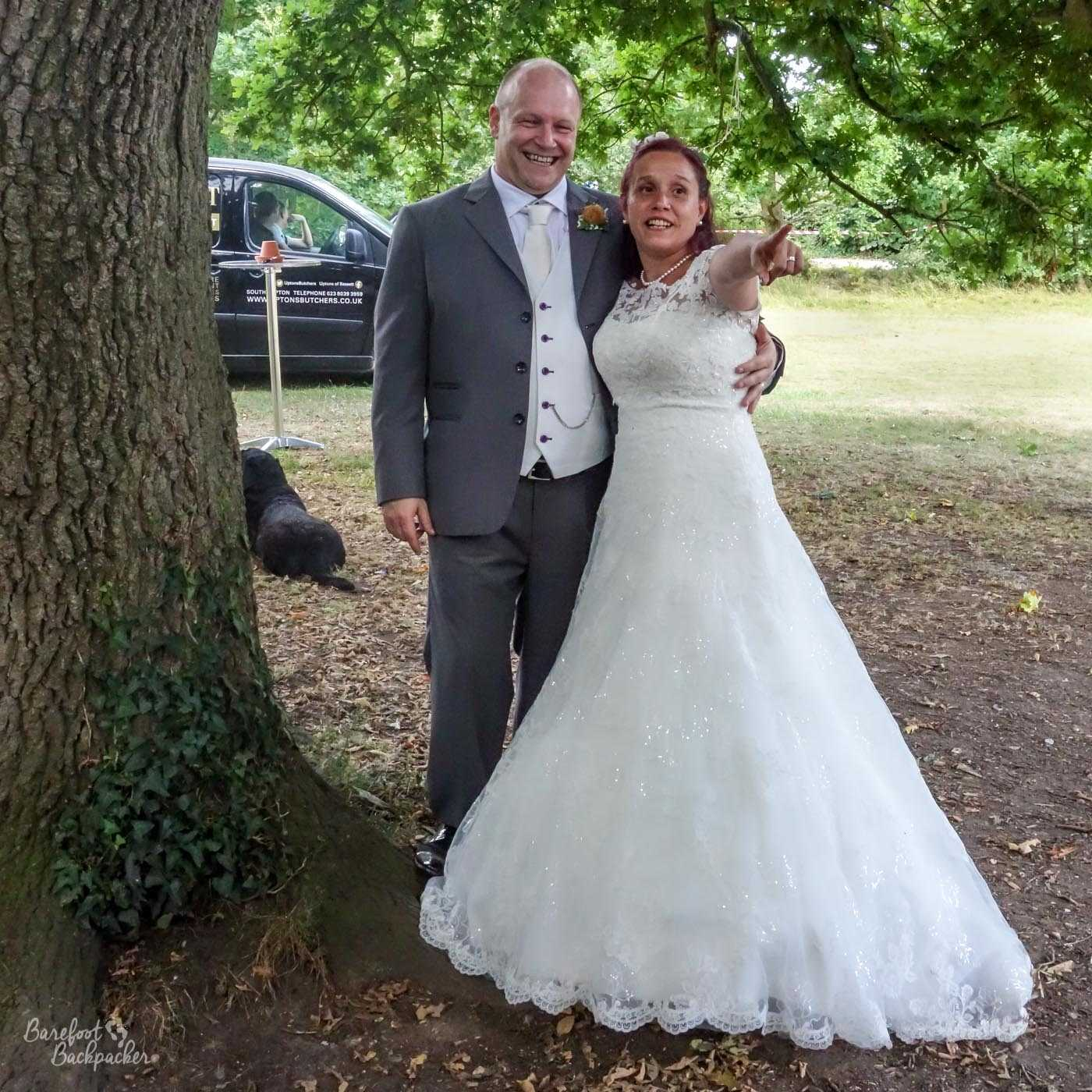 A just-married heterosexual couple – the man in a suit, the woman in a white wedding dress – standing under a tree. The woman is pointing towards the camera.