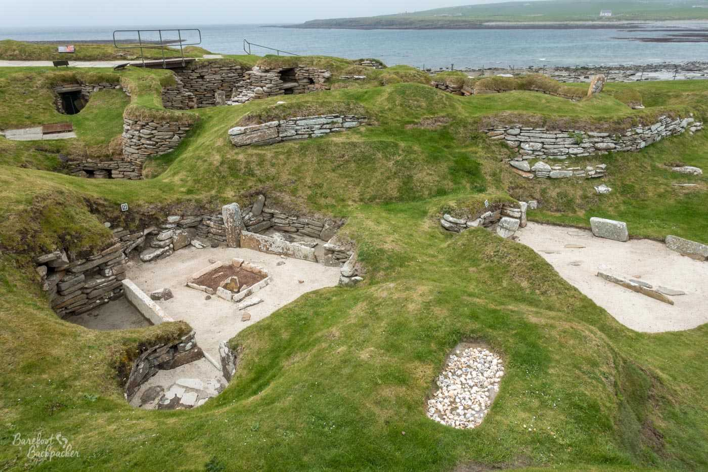The remains of several sunken houses in the undulating grassland; a bay of the sea is visible in the background.