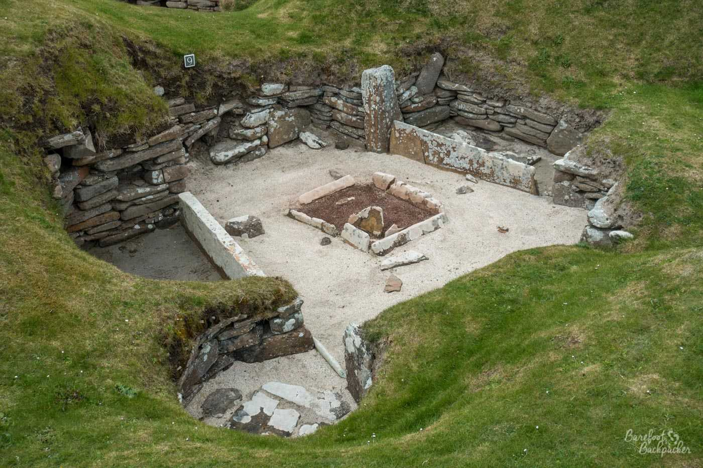 Close-up view of one of the sunken houses. There's a main 'room', with a stoned-off section in the middle that's presumably a hearth, and a four or five 'rooms' off it, smaller, delineated by the flat flagstone walls.
