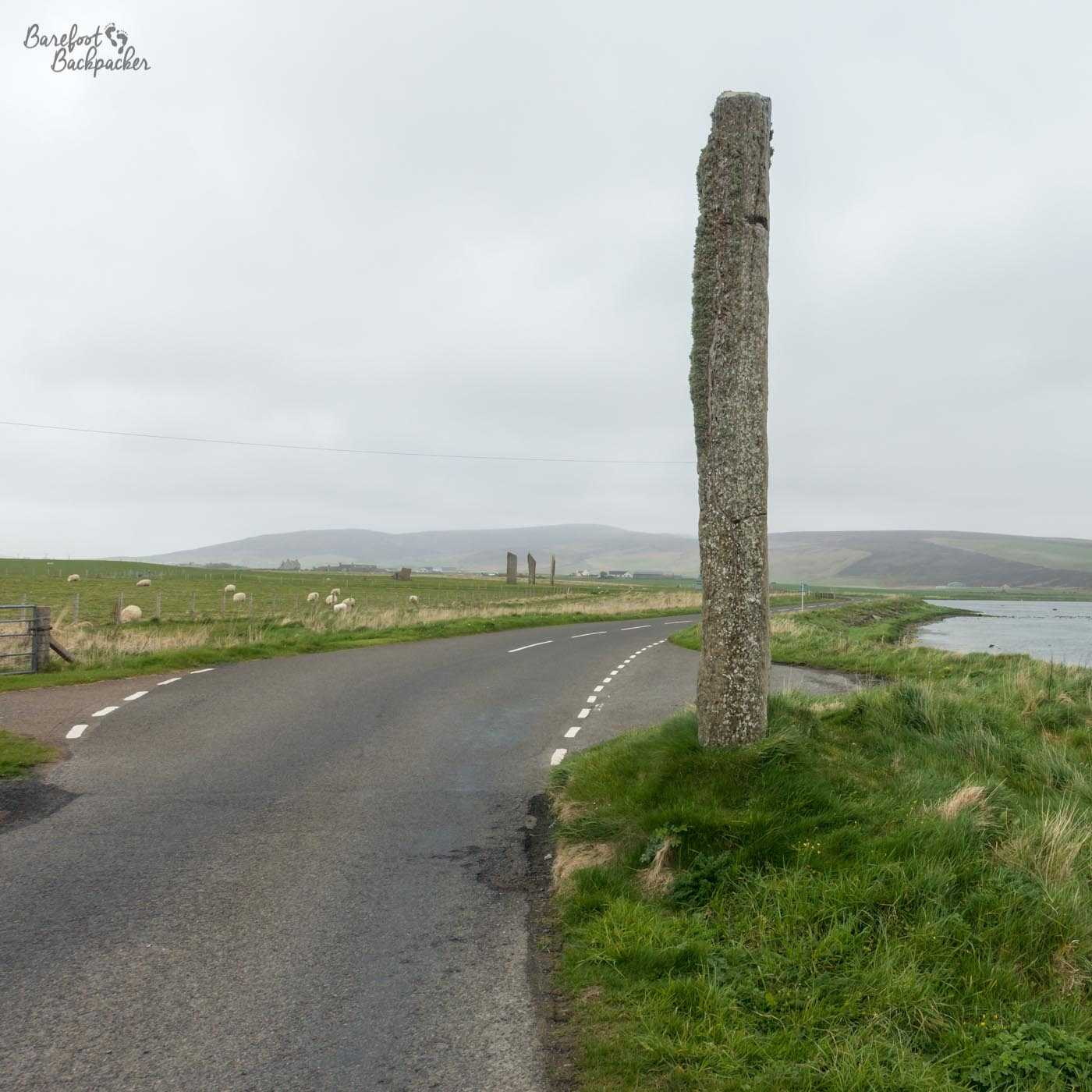 A road runs between a field and a loch. In the distance are three large standing stones. In the foreground to the right of the road is a huge solitary stone, much taller than anything else around.