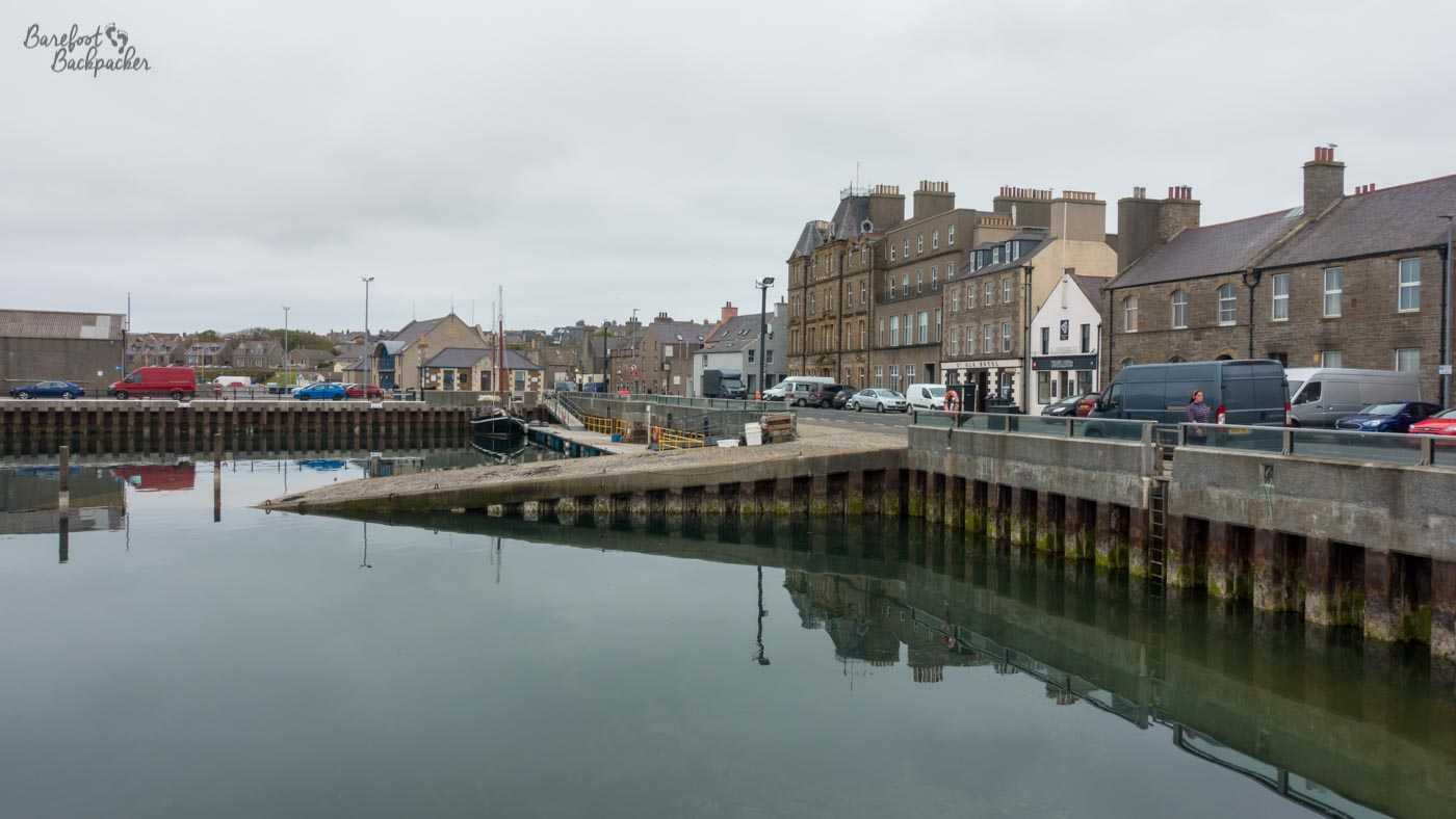 An overview of Kirkwall, near the harbour. The quayside is to the right, with a road and buildings beyond it. The water ends right at the concrete quayside. In centre view is a small slipway into the water, and behind it a kind of very wide pier with cars on it starts and heads to the left.