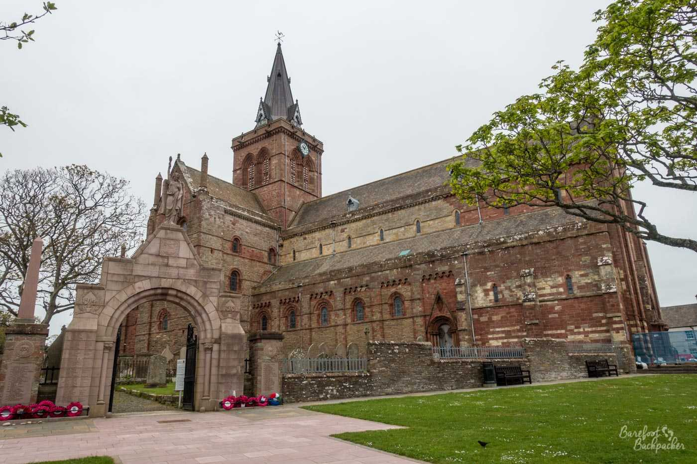 The outside of Kirkwall Cathedral; a large building built with several sections each with a pointed roof. In the background is the tower. In the foreground to the left is the entrance archway. There are remembrance wreathes on the wall near the arch.