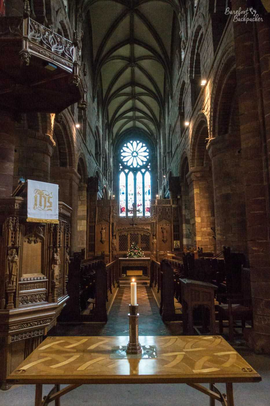 The inside of Kirkwall Cathedral looking along the main aisle towards the altar. Columns topped with arches line either side, and presumably there are seats for the choir etc below them. In the foreground is a table with a lit candle on it.
