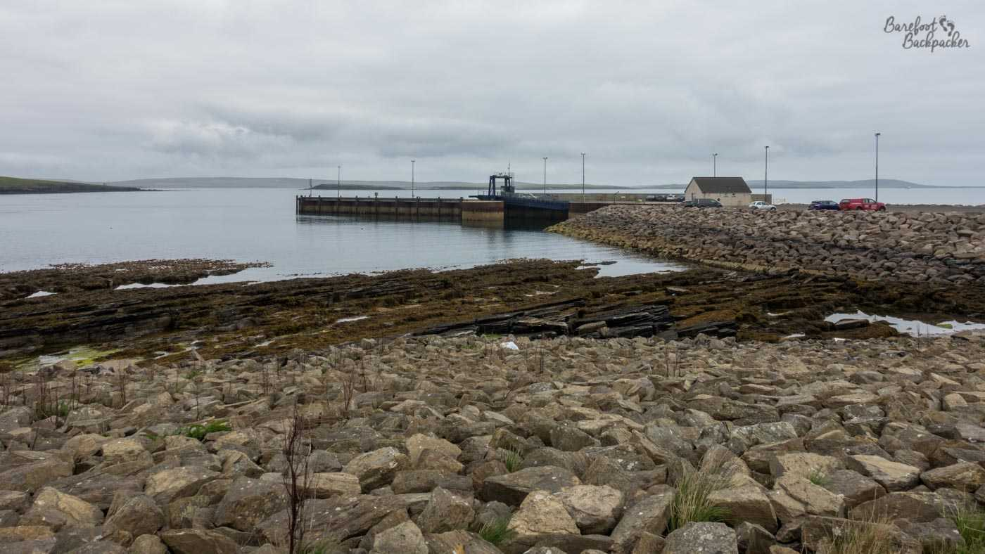 Westray Ferry Terminal. In the foreground are a series of small rocks/boulders that people could have fun scrambling over. There's a causeway to the right, built up with stone, and in the mid-ground centre is a pier that jets out onto the sea.