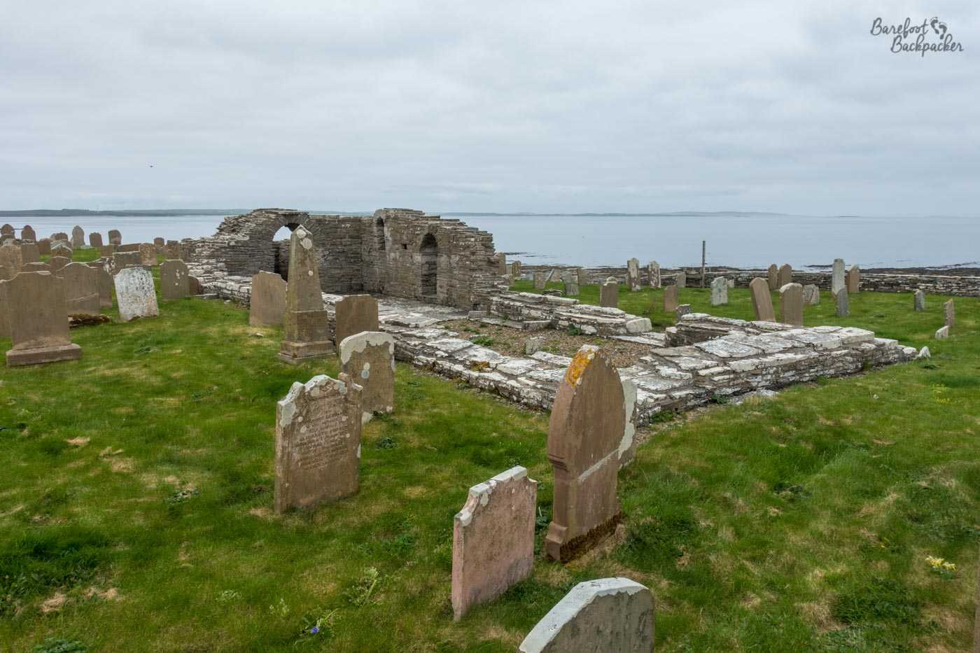 The graveyard and ruins of Cross Kirk, on Westray. The graves are old stone, and pockmarked with … guano, let's say guano. The church itself is little more than a rectangle of piled stone marginally higher than the surrounding graveyard, inside which is a gravel floor. At one end of the church are structurally taller remains, big enough to have a couple of archways visible. Behind is the sea.