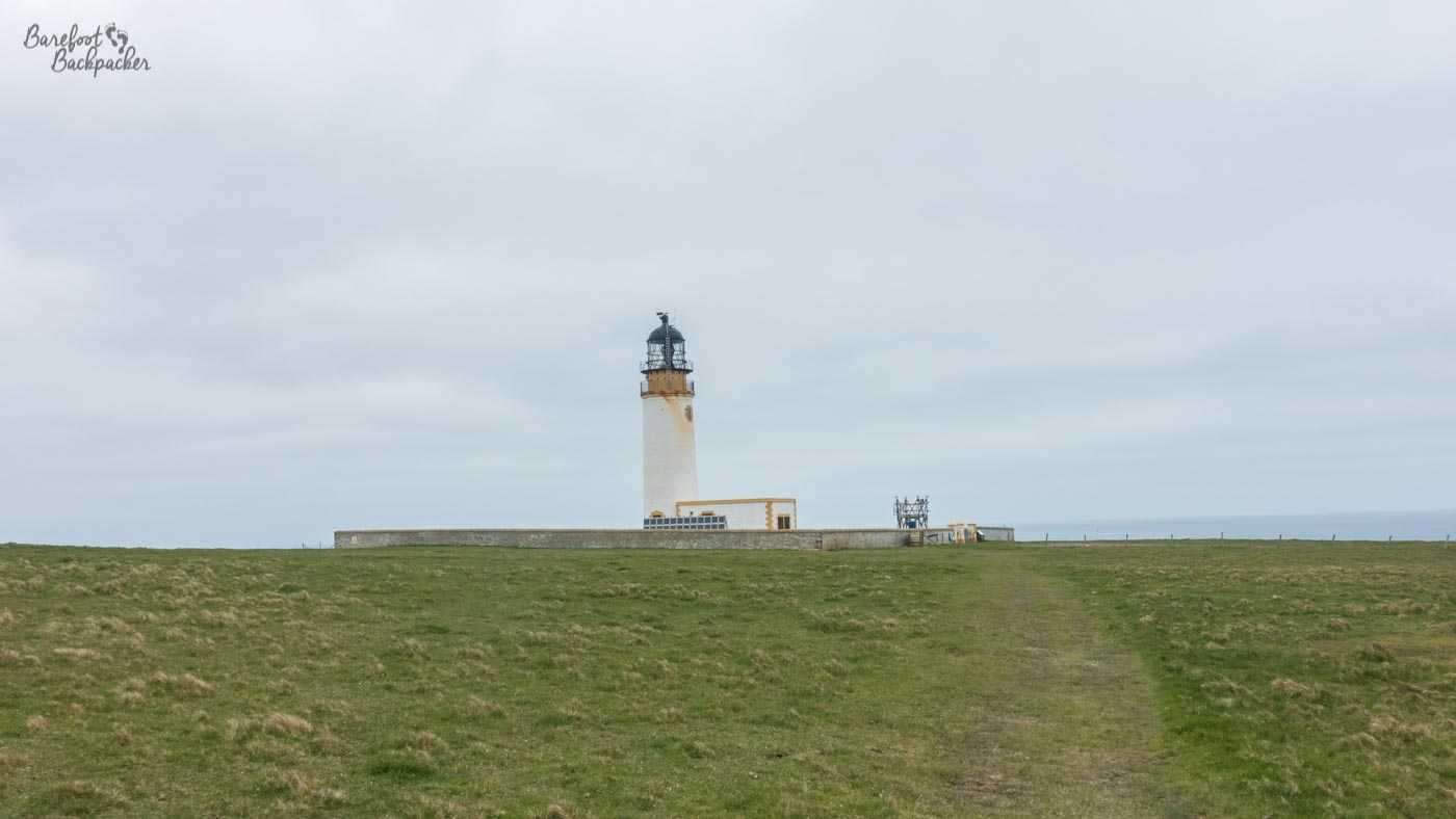 Noup Head Lighthouse. A simple white tower with a light in a cage at the top, set on a flat cliffside. There's nothing else here.