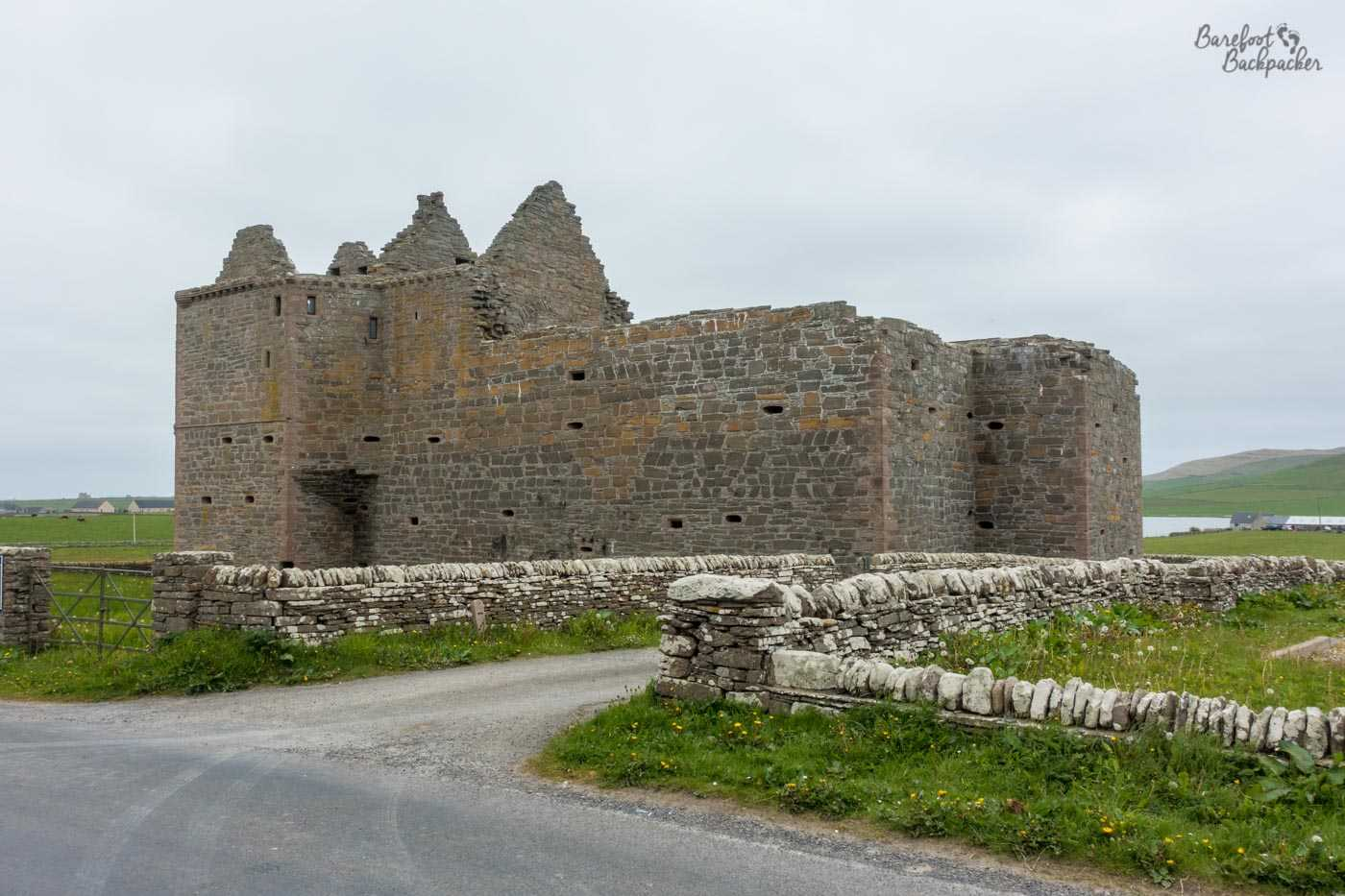 Noltland Castle, ruins of. Four walls, in a kind of cuboid shape, the left hand side of which has slightly raised diagonals on which sat a roof. There is no roof. The castle is in a small field surrounded by a low stone wall.