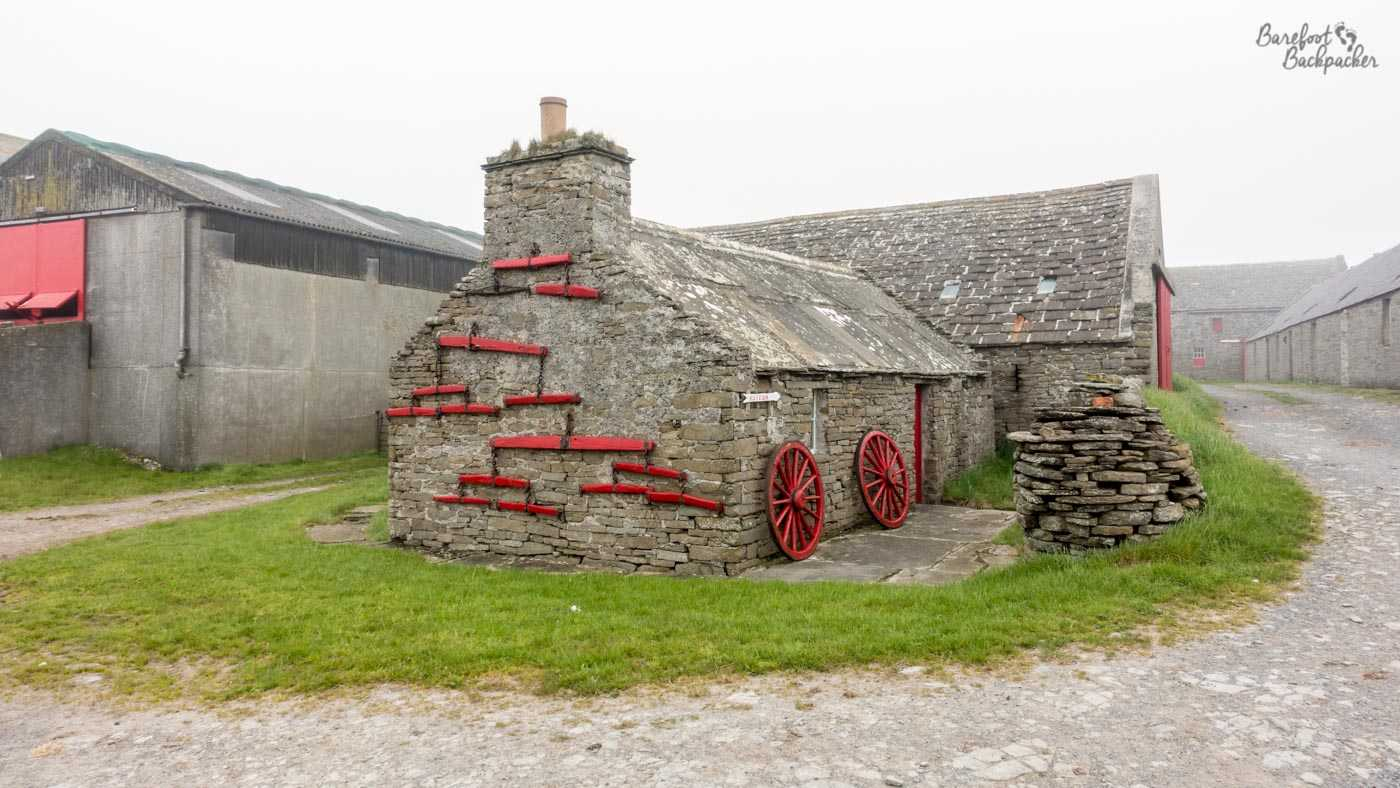 Stone cottages, one of which has a series of red wheels and red farm parts attached to the wall.