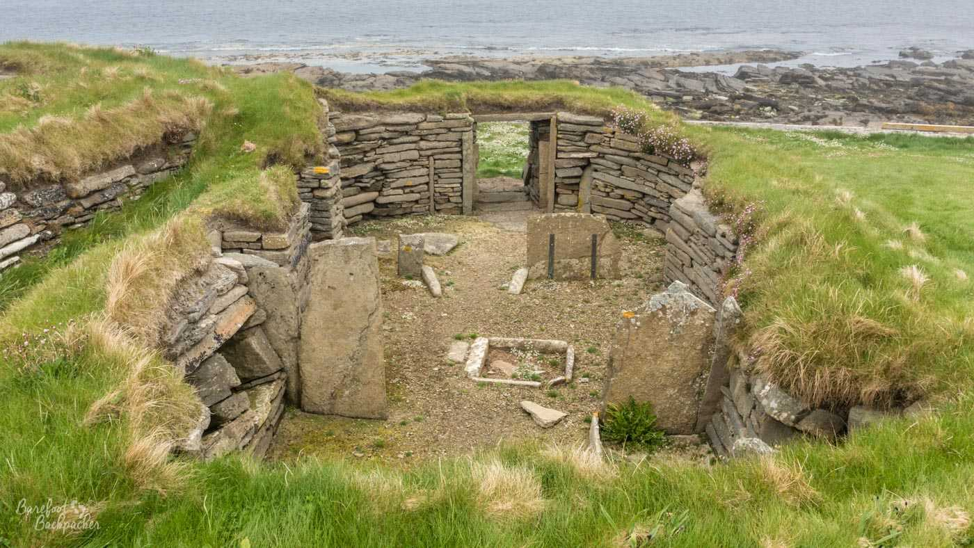 A sunken house - a depression in the grass on a cliff edge is lined with flagstones. The area contained within is gravelled and has some stone ornamentation.
