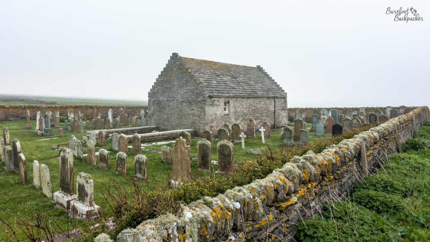 On a grey day, the picture is taken from just outside the old walls of the churchyard. The church is a small rectangular stone building and is surrounded by many many rows of graves.