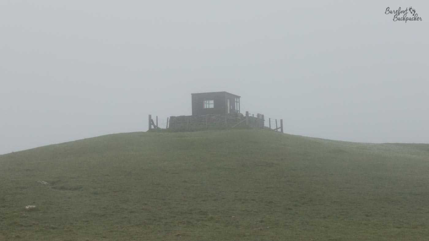 A small hut is just about visible on the top of a hill; everything else is fog.