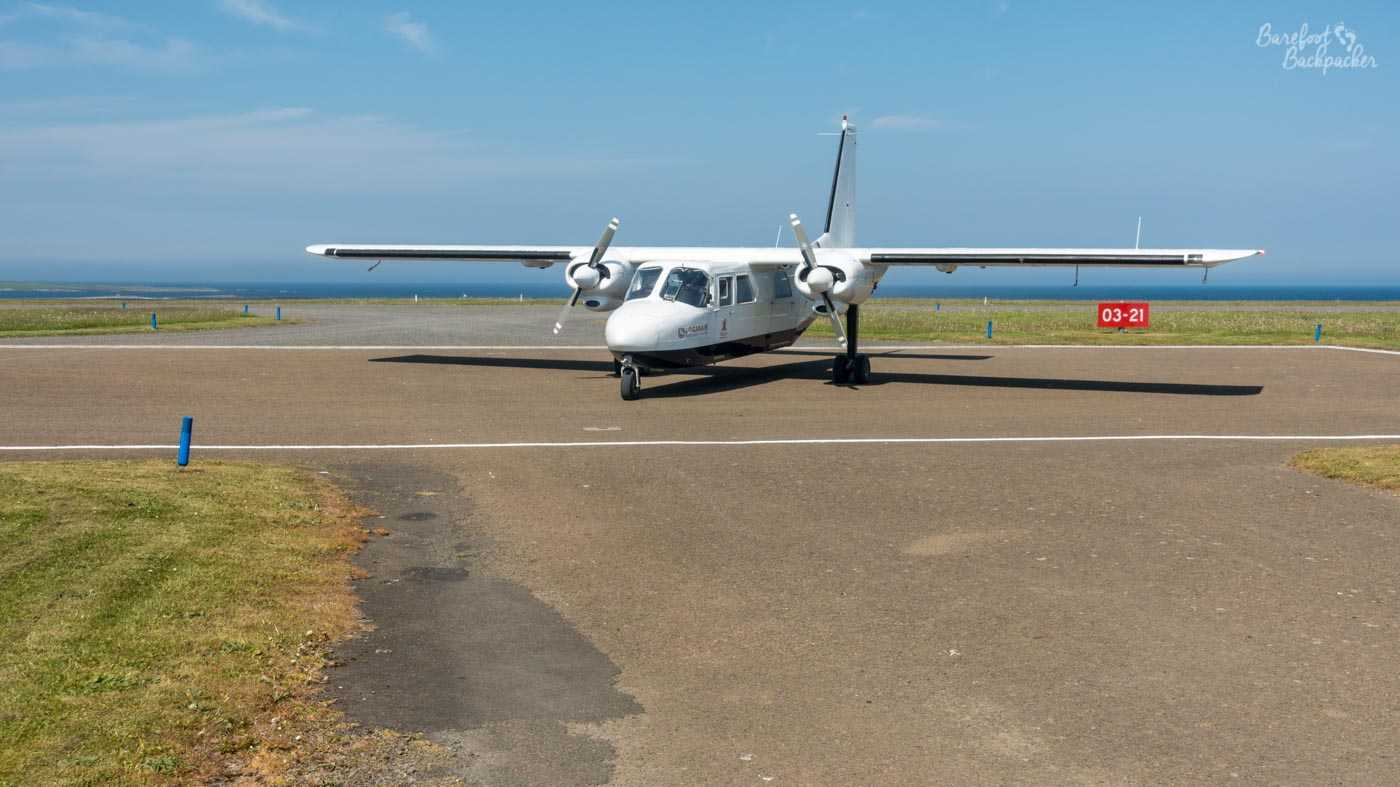 An inter-island aeroplane at Papa Westray airstrip. It's an 8-seater propeller plane, and it stands on a strip of tarmac in a field that's been designated as a runway.