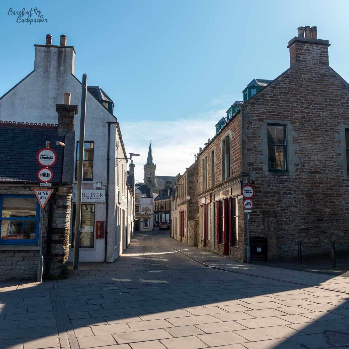 Picture of the town centre of Stromness. There are brick and stone buildings on a square, either side of a road. All the roads are paved with flat flagstones rather than tarmac. In the distance down the street is a church spire.