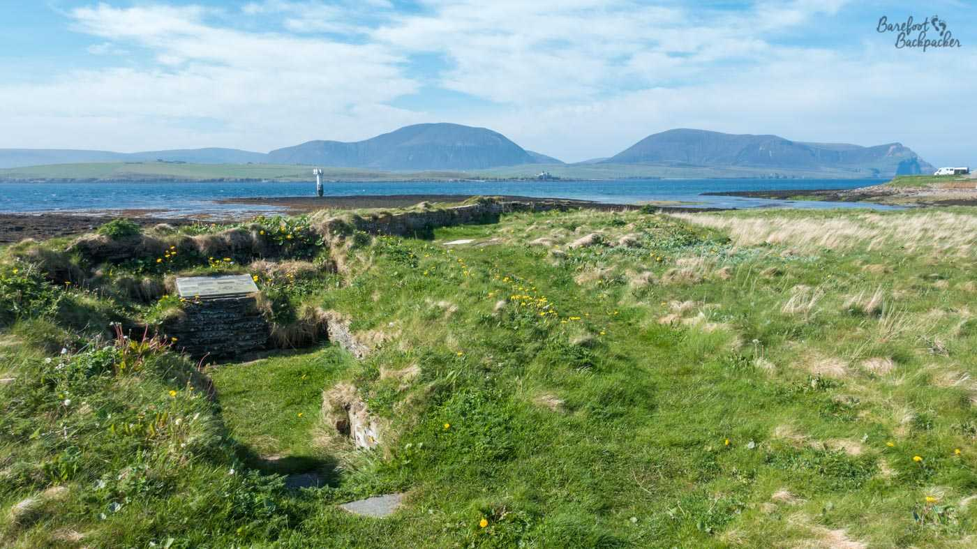 Some of the limited ruins of the Ness Battery area. It's basically a couple of stone foundations partly hidden under the machair, the grassy/flowery dune landscape of coastal Scotland. There's an information board in the mid-foreground. The sea is in the background, and behind that are the misty faded outlines of the hills of Hoy.