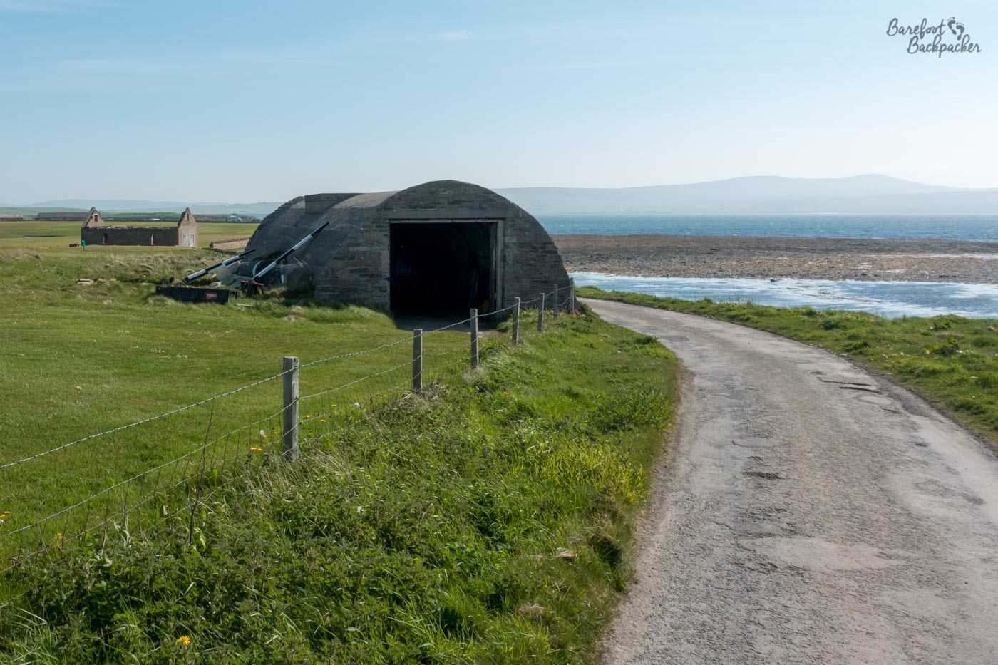 Military ruins on the cliff edge near Stromness, on Orkney Mainland. It's a rounded Nissen Hut near the ruins of an artillery, it's now farming storage.