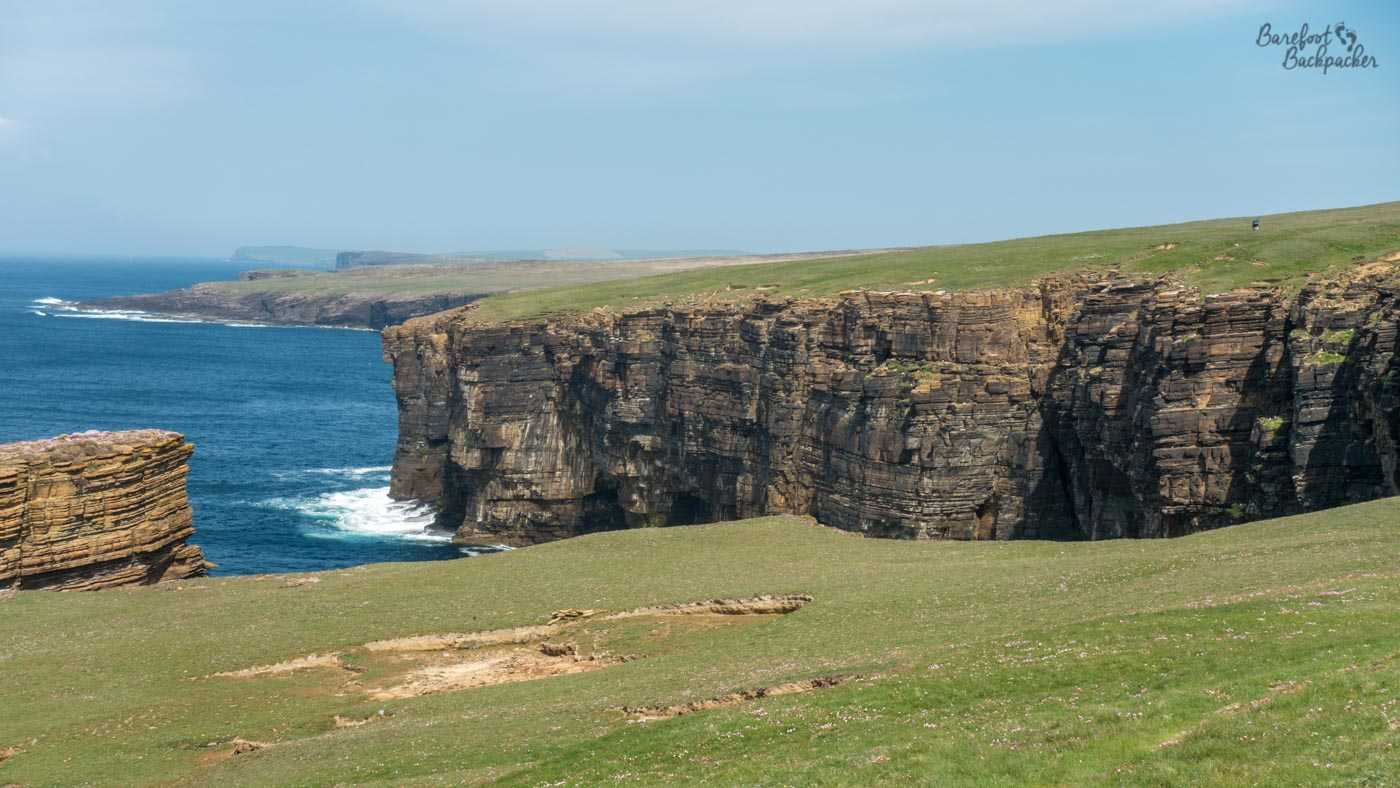 The rocks and indented coastline of Orkney Mainland. In front of camera is a grassy cliff, which then drops to a fjord. The rock cliff face on the far side of the fjord can be seen, layered, but still foreboding. On top of that cliff is more grass, and the land sticks out to the left. Both behind that, and to the left of shot, are more cliffs and fjords; the landscape isn't straight.