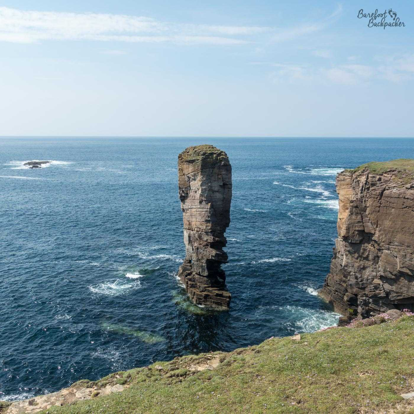 Rising up from a slightly choppy sea, beyond the cliff edge, is a tower of rock. It's bare and thinner at the bottom, wider towards the top, and the very top of it is covered with a layer of moss. From a certain angle, it has the profile of a man's elongated face.